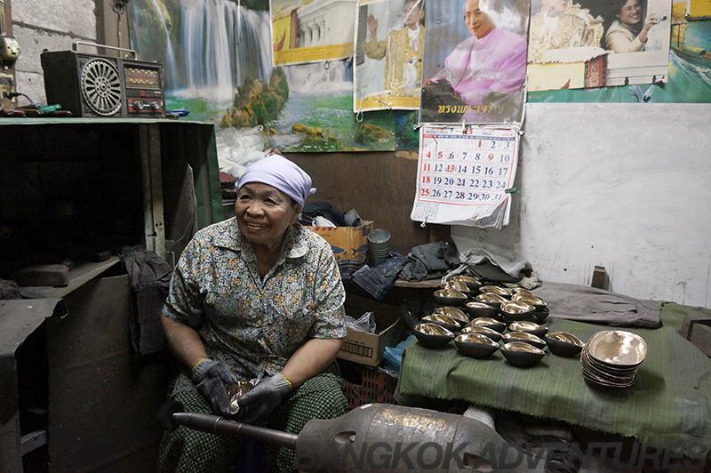 Skilled lady polishing the metal bowls to a high shine.